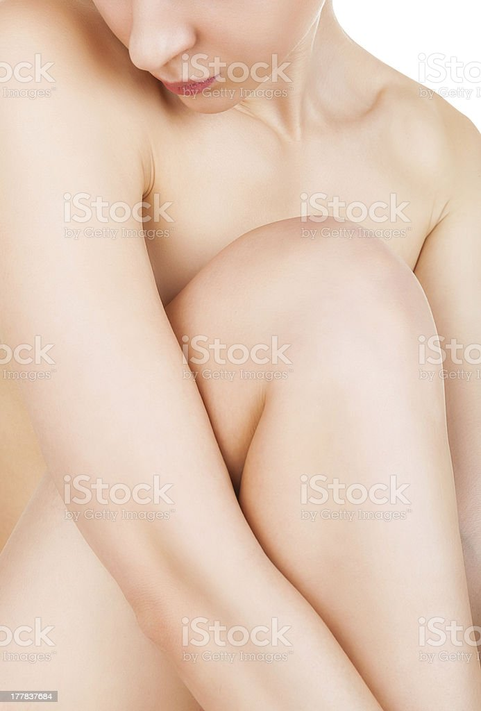 A nude female hugging her legs stock photo