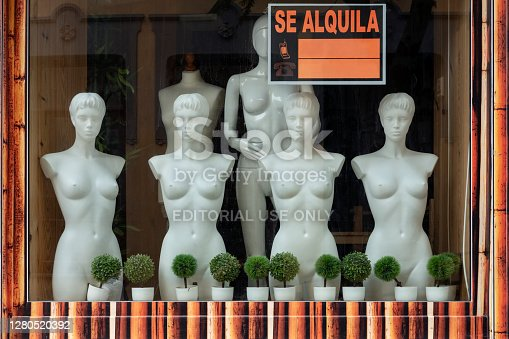 Puerto de la Cruz, Tenerife, Canary Islands, Spain - June 11, 2020: nude female mannequins or plastic dummies in an empty shop window with an orange sign reading Se Alquila or For rent and plant pots.