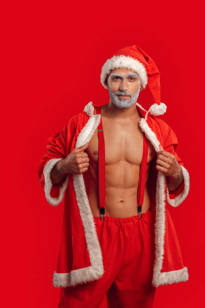 nude santa claus takes off the costume - naked santa claus stock pictures, royalty-free photos & images