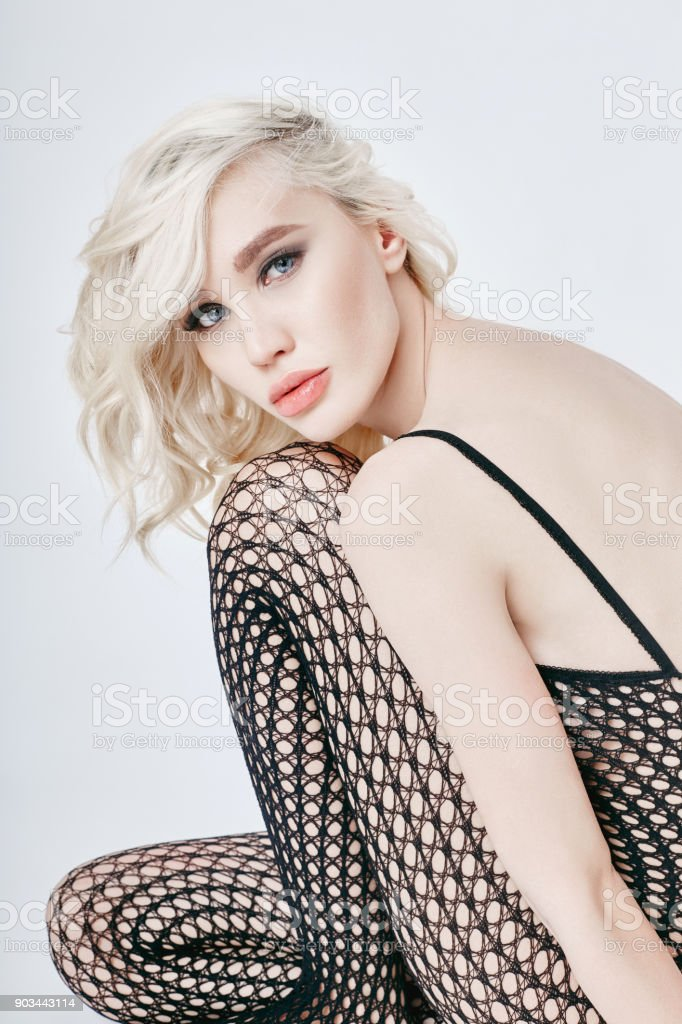 Nude sexy blond woman in lingerie bodysuit with a perfect body sitting on  the floor. Fetish lingerie into the net on erotic girl.