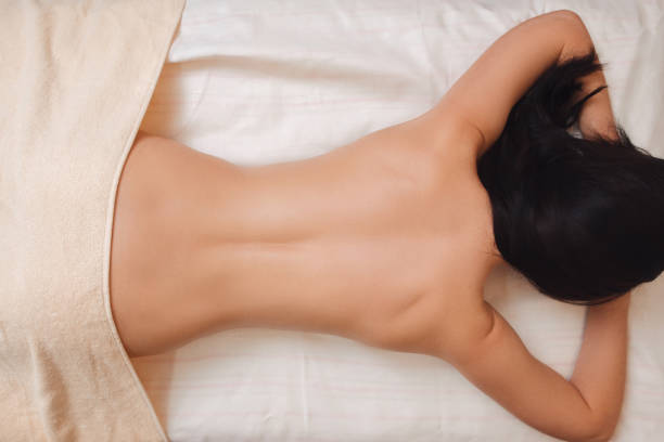 nude woman back on massage table flat lay - espalda humana fotografías e imágenes de stock