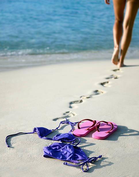 nackte frau gehen sie schwimmen - fkk strand stock-fotos und bilder