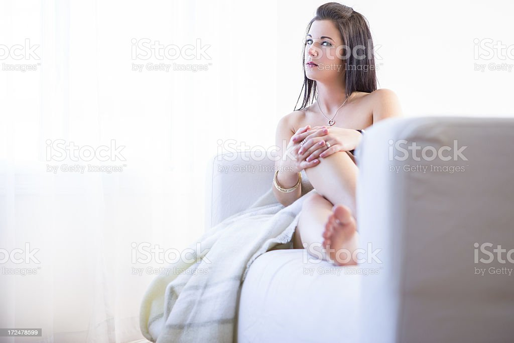 Nude woman hugging blanket looking out window royalty-free stock photo