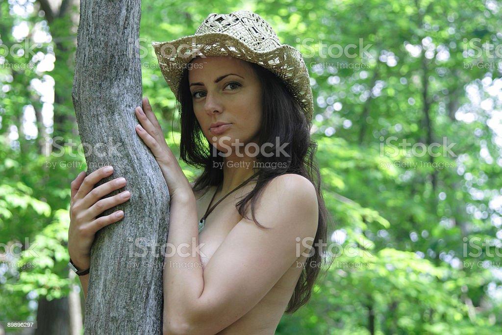 Телесный женщина в шляпе, скрытые под дерево в лесу Стоковые фото Стоковая фотография