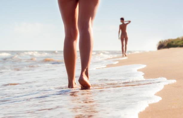 nackte junge mädchen gehen am strand in den wellen der brandung an einem sommertag - fkk strand stock-fotos und bilder