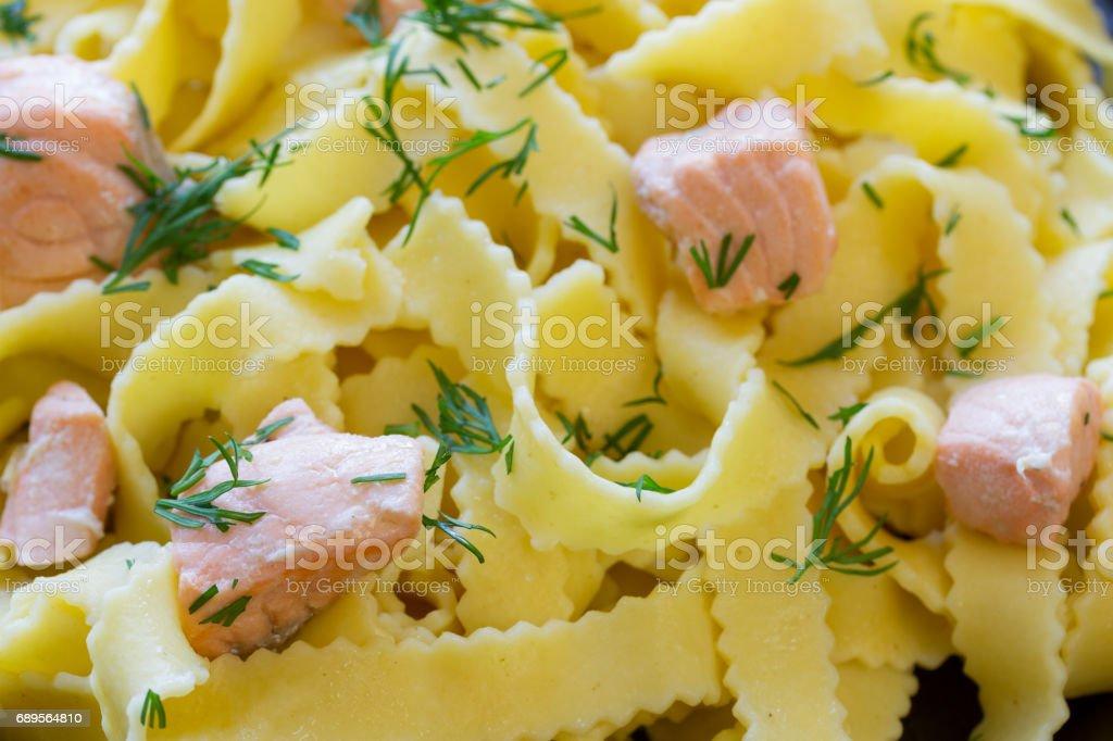 Nudeln mit Sahnesoße und Lachsstücken stock photo