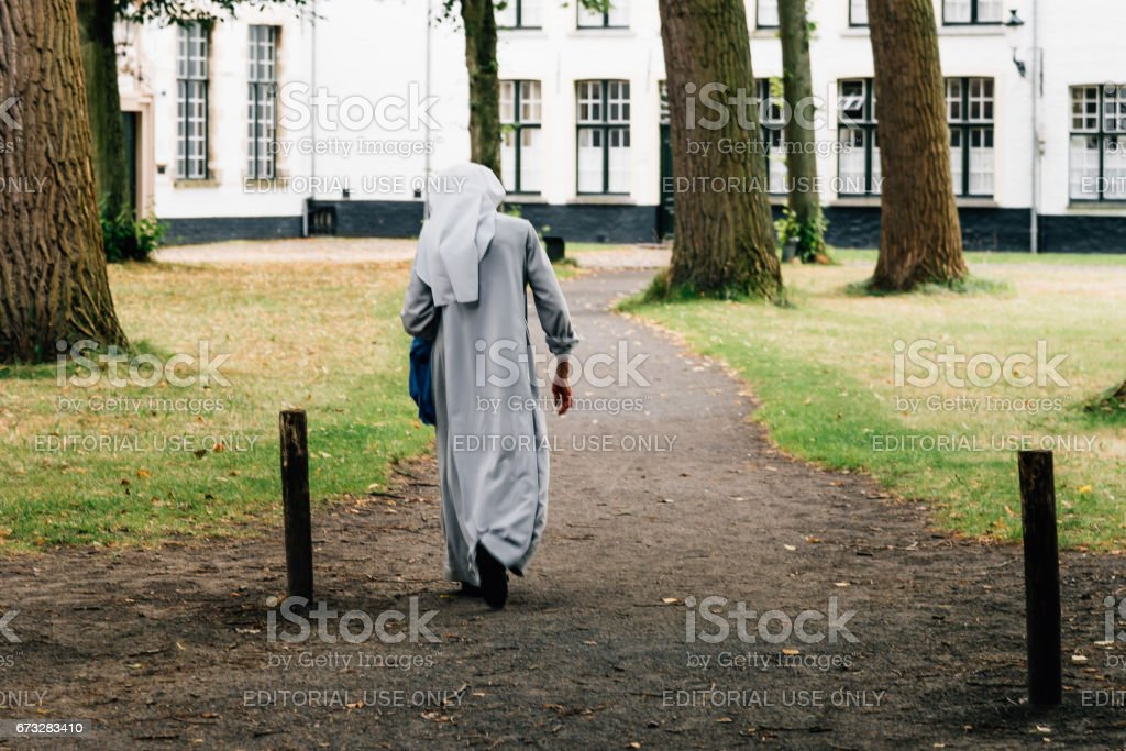 Num walking on the park in the beguinage of Bruges stock photo