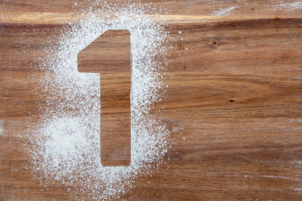 Number 1 stencil in flour on a wooden board stock photo