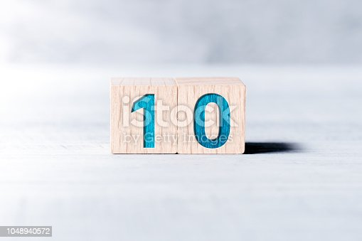Number 10 Formed By Wooden Blocks On White Table