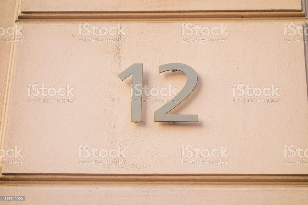 number 12 door sign on orange facade stock photo