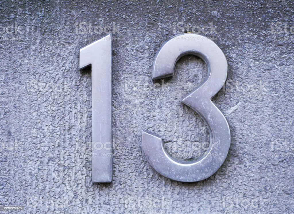 Number 13 on brick wall, background, rustic and grunge wall stock photo