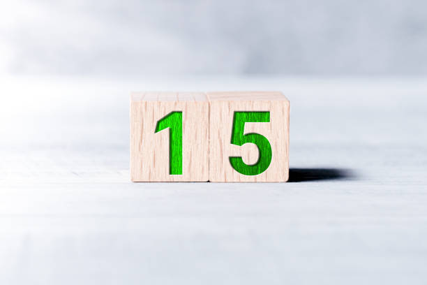 Number 15 Formed By Wooden Blocks On A White Table stock photo