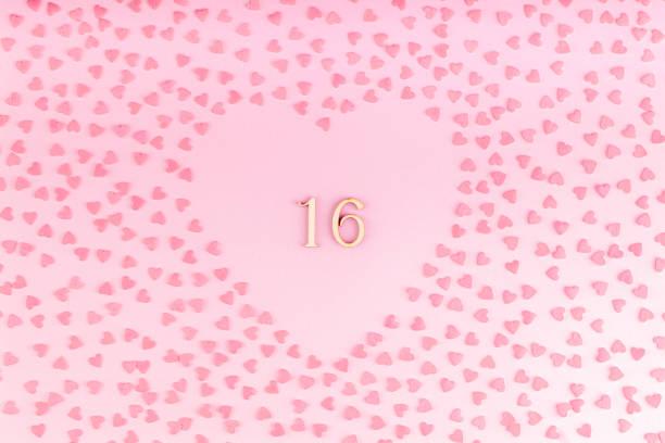 nummer 16 sechzehn aus holz in herzförmigen dekoration mit kleinen herzen - glückwünsche zum 16. geburtstag stock-fotos und bilder