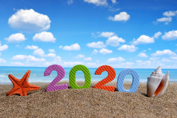 Number 2020 and sea shell with starfish on the beach. stock photo