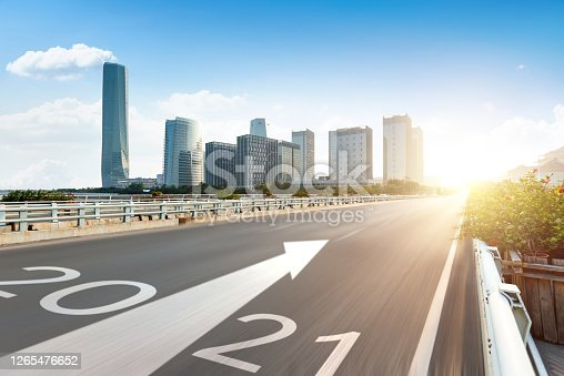 Number 2021 on empty elevated road with modern cityscape in the background