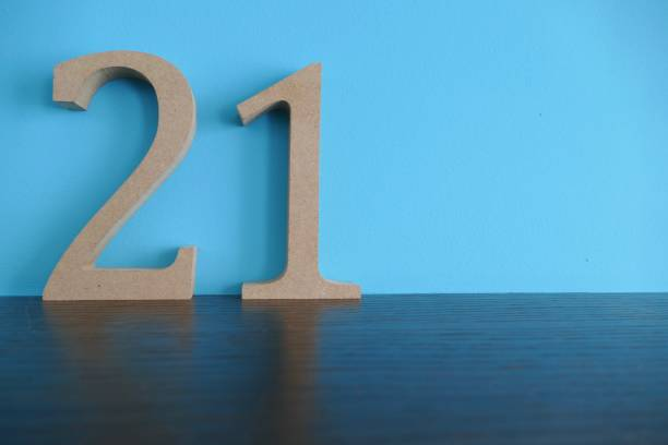 number 21 in wooden numbers on blue background - number 21 stock photos and pictures