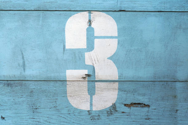 number 3 on old wood dilapidated wall. white symbol with scratches on blue background - terceira imagens e fotografias de stock