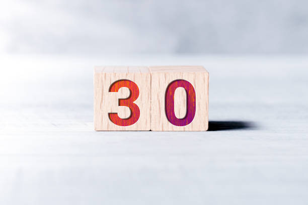 number 30 formed by wooden blocks on a white table - number 30 stock photos and pictures