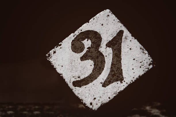 number 31 painted on a white concrete cube with a dark brown blurred background stock photo