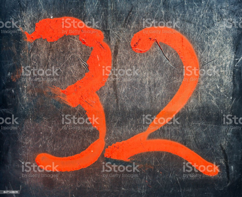Number 32 poorly painted in bright orange on concrete stock photo
