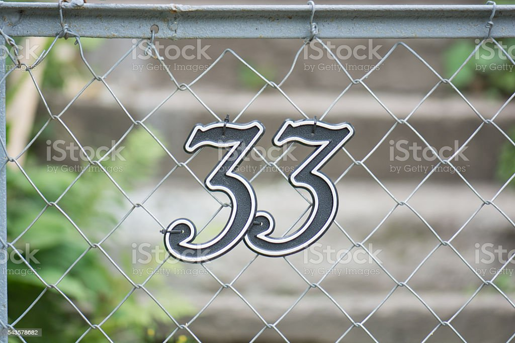 Number 33 on a fence stock photo