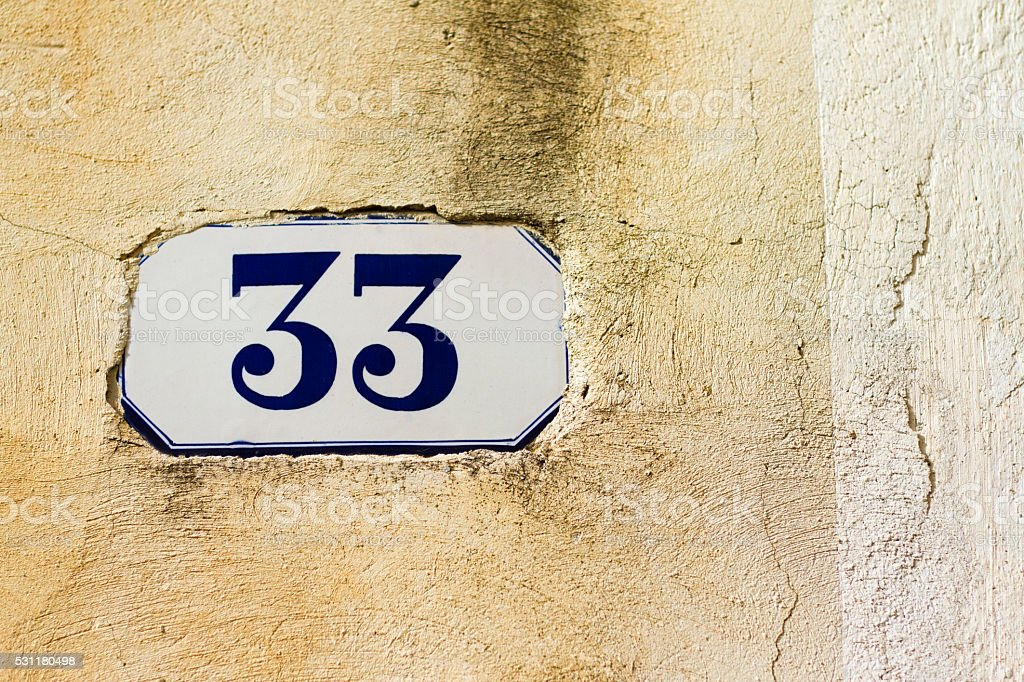 Number 33 Street Address Tile On Old Yellow Wall stock photo
