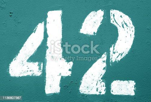 istock Number 42 in stencil on rusty metal wall in cyan tone. 1136807367