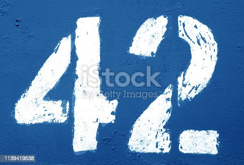 istock Number 42 in stencil on rusty metal wall in navy blue tone. 1139419538