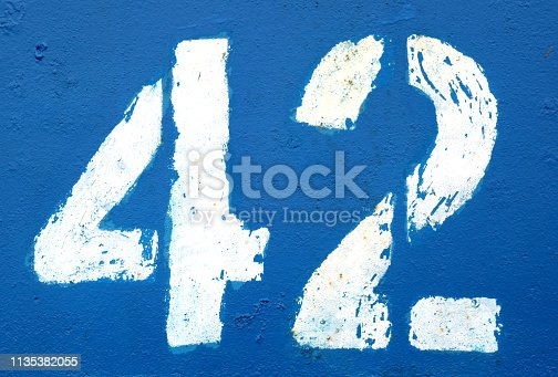istock Number 42 in stencil on rusty navy blue metal wall. 1135382055