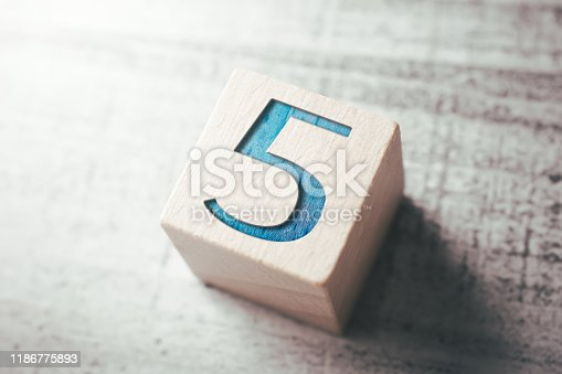 The Number 5 On A Wooden Block On A Table