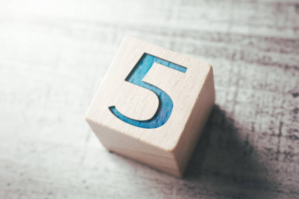 number 5 on a wooden block on a table - numero 5 foto e immagini stock