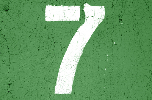 Number 7 in stencil on metal wall in green tone. Abstract background and texture for design.