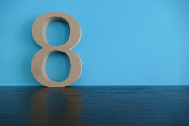 number 8 in wooden numbers on blue background - number 8 stock pictures, royalty-free photos & images