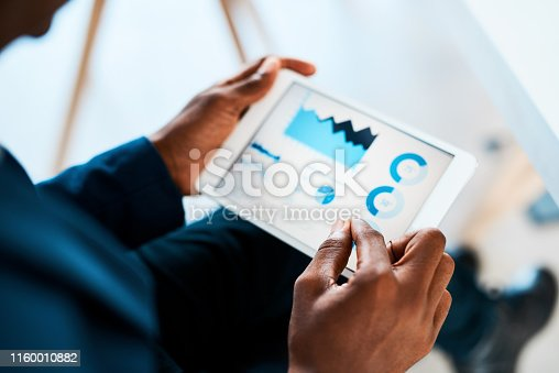 Cropped shot of a businesswoman using a digital tablet with graphs on it in a modern office