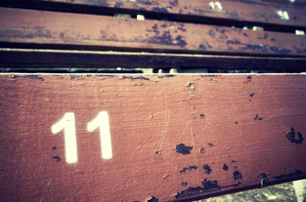 Number eleven painted on an old wooden seat. stock photo