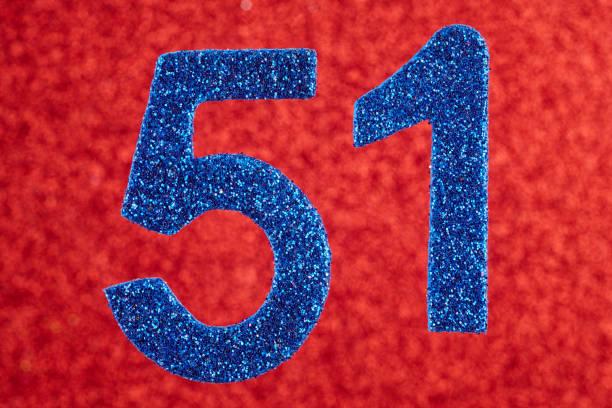 número cincuenta y uno azul sobre un fondo rojo. aniversario. - numero 51 fotografías e imágenes de stock