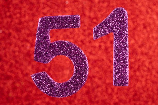 número cincuenta y uno púrpura sobre un fondo rojo. aniversario. - numero 51 fotografías e imágenes de stock