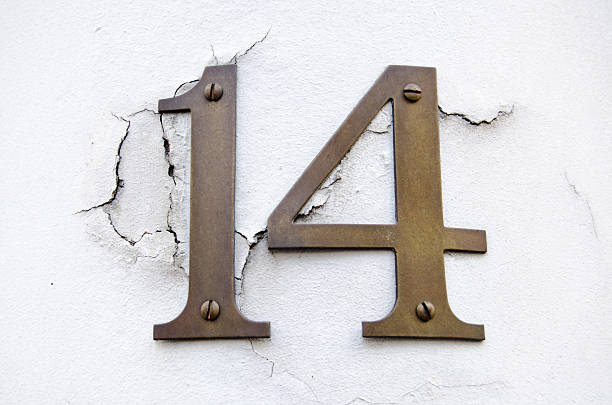 Number fourteen on cracked wall stock photo