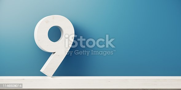 Number nine is standing in front of blue wall. Horizontal composition with copy space.