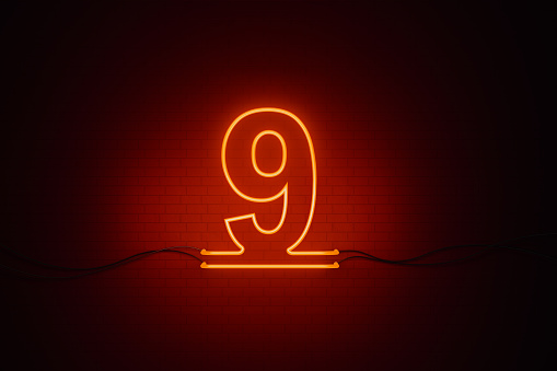 Number nine written by red neon light on black wall. Horizontal composition with copy space.