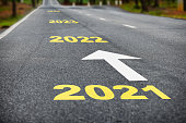 istock Number of 2021 to 2024 on asphalt road surface with white arrow 1250440018
