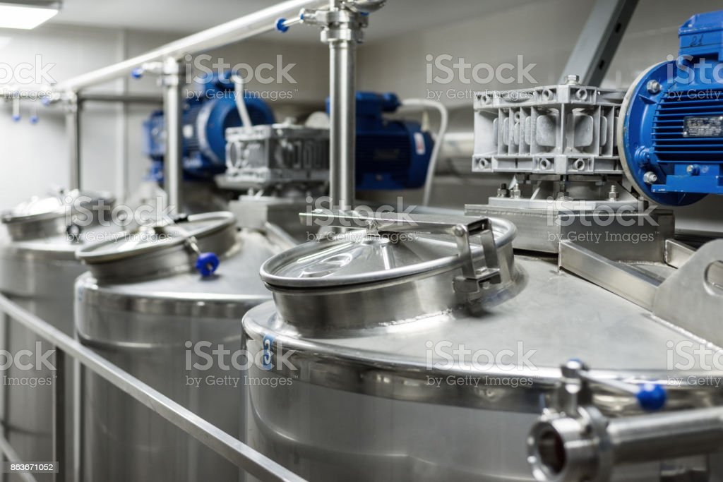 A number of electric motors with reducers. Tanks for mixing liquids stock photo