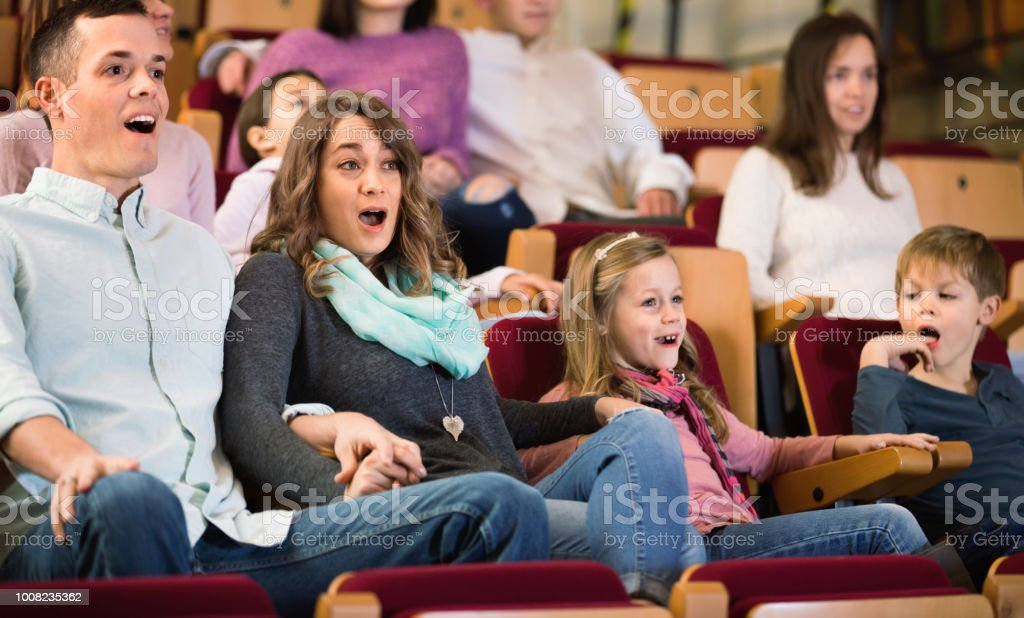 Number of cheerful positive people enjoying exciting film in in...