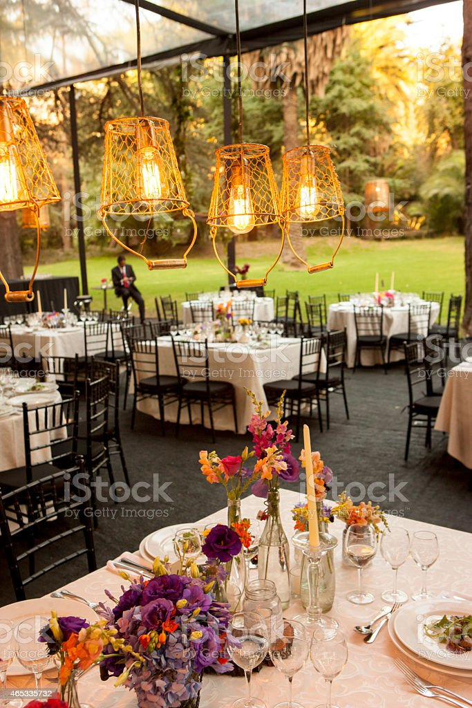 A number of tables set outside with luxury settings stock photo