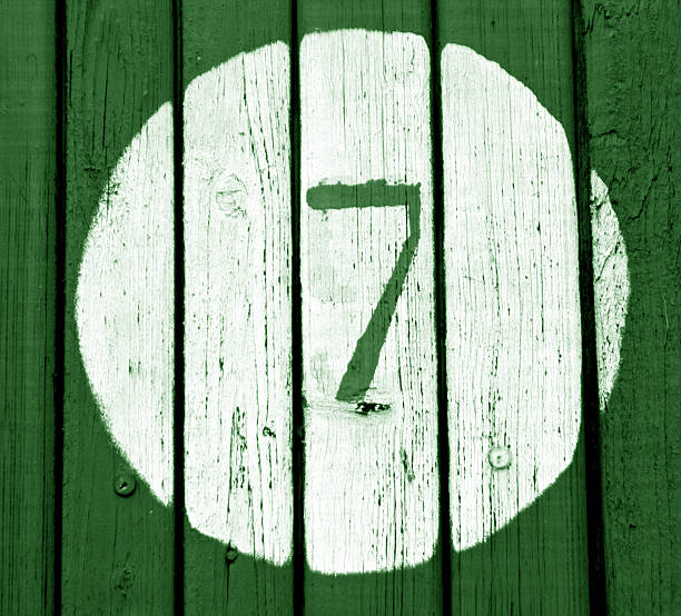 Number seven on green toned wooden wall stock photo