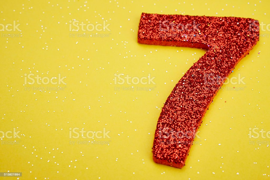Number seven red color over a yellow background. Anniversary stock photo