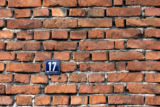 Number seventeen, a metal sign on a red brick wall stock photo