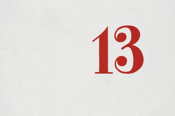 zahl dreizehn an weißer wand - number 13 stock-fotos und bilder