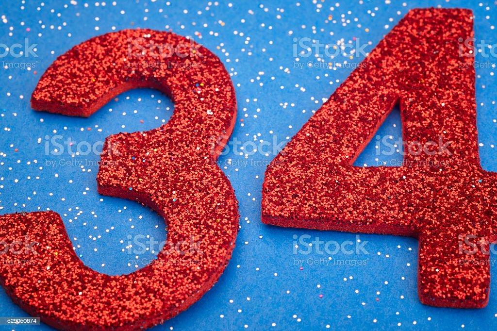Número thirtyfour Color rojo sobre un fondo azul. Aniversarios - foto de stock