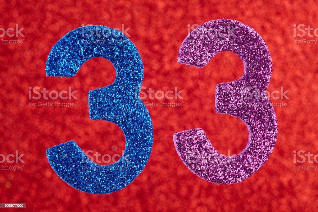 Número treinta y tres de color morado azul sobre un fondo rojo - foto de stock